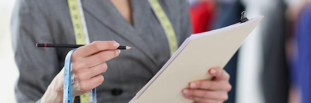 Vrouw naaister metingen op papier opschrijven met potlood close-up vrouwelijke bedrijfsconcept