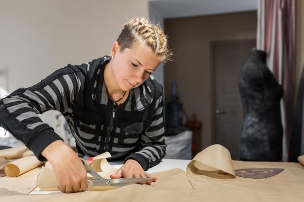 Vrouw naaister snijdt van ambachtelijke papieren patroon voor het maken van kleding