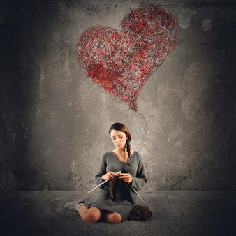 Vrouw naait om een groot hart te haken