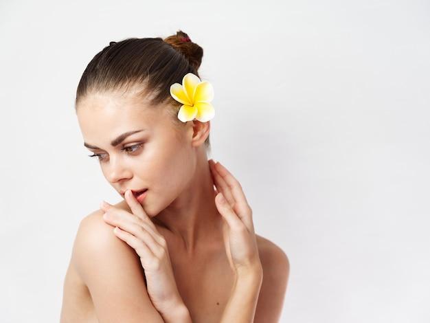 Vrouw naakte schouders cosmetica bijgesneden weergave gele bloem