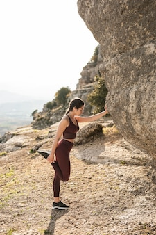 Vrouw naast berg opwarmen voor yoga