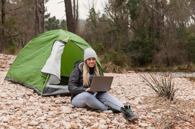 Vrouw naast tent met laptop