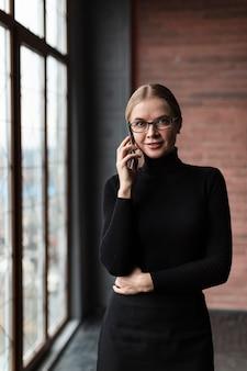 Vrouw naast venster dat over telefoon spreekt