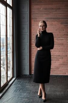 Vrouw naast venster praten via de telefoon