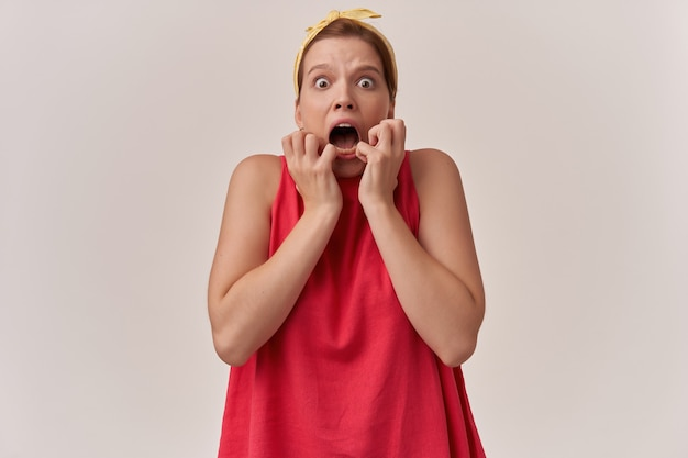Vrouw natuurlijke make-up emotie beklemtoond vreselijk angstaanjagend vreselijk angstig vreselijke paniek met vuisten op gezicht dragen van modieuze rode blouse en witte bandana