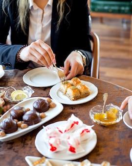 Vrouw neemt baklava om te eten met thee