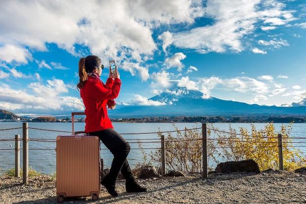 Vrouw neemt een foto bij fuji-bergen. herfst in japan. reis concept.