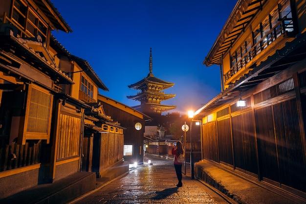 Vrouw neemt een foto bij yasaka pagoda en sannen zaka street in kyoto, japan.