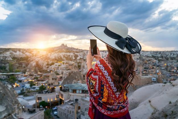 Vrouw neemt een foto met haar smartphone in goreme, cappadocië in turkije.