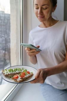Vrouw neemt een foto op slimme telefoon, met bord met knapperig roggebrood met kaas en microgreens