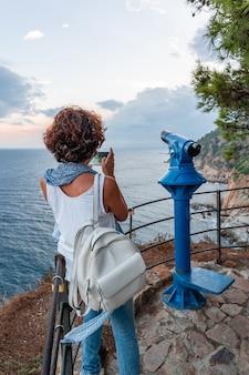 Vrouw neemt een foto van het kustlandschap met haar smartphone, vanuit een gezichtspunt