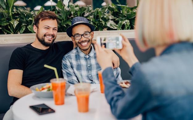 Vrouw neemt een foto van opgetogen multiraciale mannen