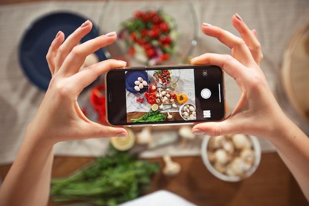 Vrouw neemt een foto van verschillende mooie groenten en groenen met een mobiele telefoon in haar keuken. smartphone food fotografie. gezond eten, vegetarisch eten, dieet. voor gewichtsverlies en detox.
