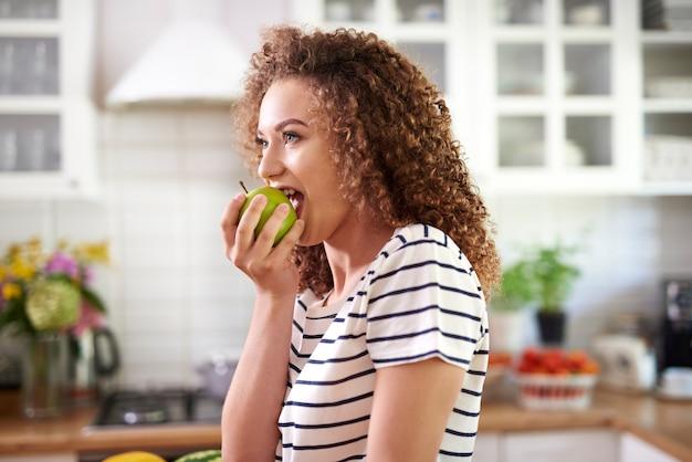 Vrouw neemt een grote hap van een appel Gratis Foto
