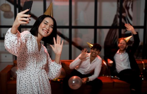 Vrouw neemt een selfie met haar vrienden op een oudejaarsfeestje