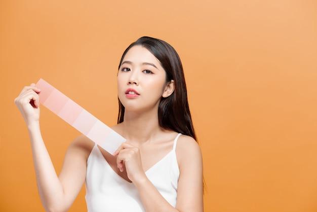 Vrouw neemt huidskleurschaal op de gele achtergrond