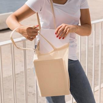 Vrouw neemt papieren uit boodschappentas