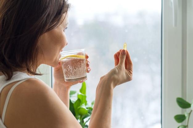 Vrouw neemt pil met omega 3