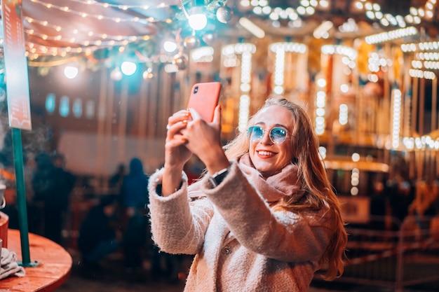 Vrouw neemt selfie op defocus achtergrondlicht in avondstraat