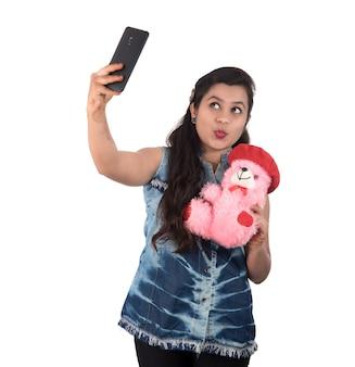 Vrouw nemen foto of selfie met mobiele telefoon en teddybeer te houden