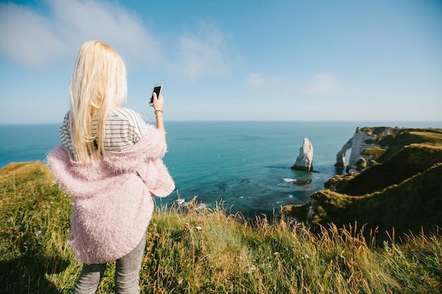 Vrouw nemen foto van een uitzicht van bovenaf naar de baai en de albasten klifbaai van etretat, frankrijk