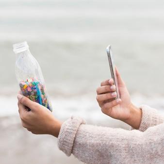 Vrouw nemen foto van fles met plastic