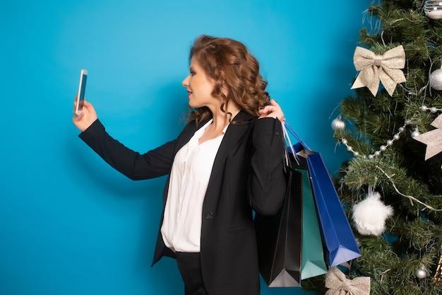 Vrouw nemen selfie op telefoon met geschenkzakken in de hand