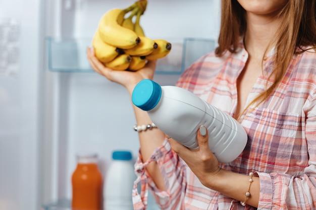 Vrouw nemen voedsel uit een koelkast close-up