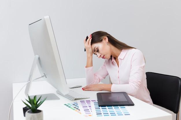 Vrouw niet gelukkig over het werk en zittend aan een bureau