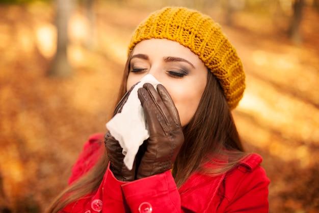 Vrouw niezen in zakdoek in de herfst