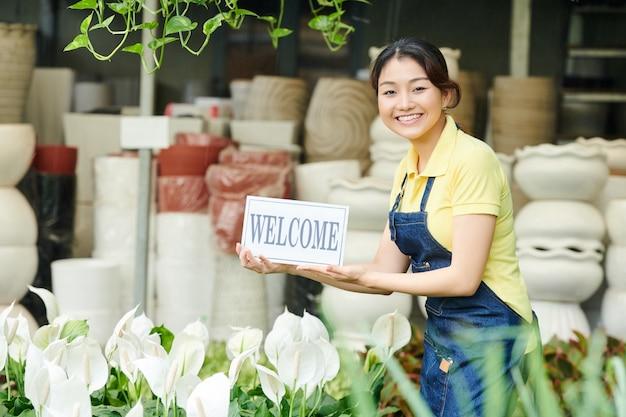 Vrouw nodigt klanten uit voor de plantenmarkt
