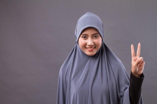 Vrouw nummer 2 omhoog, overwinning handgebaar van aziatische moslimvrouw model