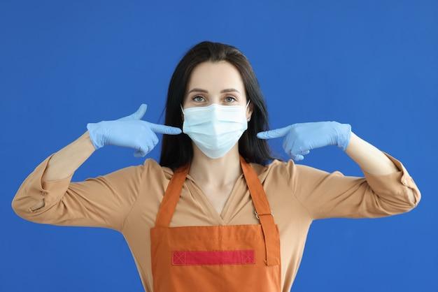 Vrouw ober in rubberen handschoenen met beschermend masker op haar gezicht