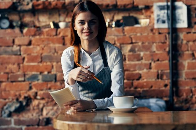 Vrouw ober koffiekopje in de buurt van de bakstenen muur van de tafel