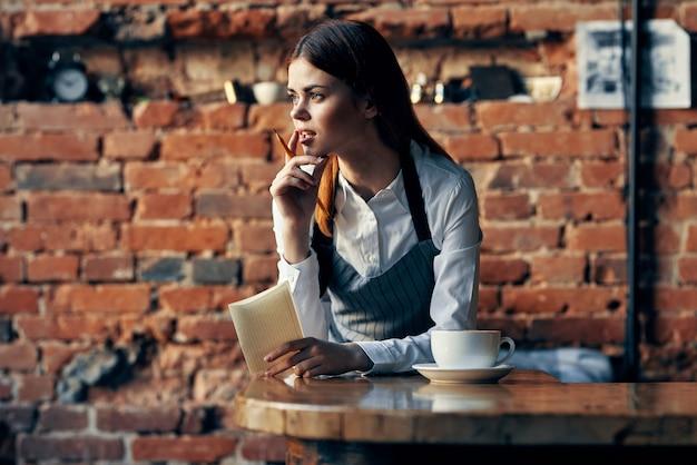 Vrouw ober koffiekopje in de buurt van de bakstenen muur van tafel