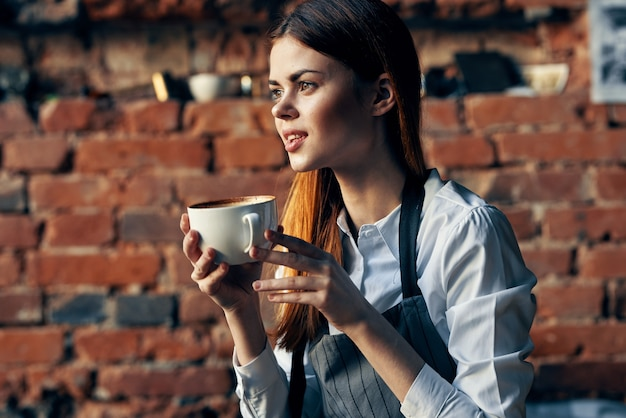 Vrouw ober koffiekopje zittend aan de tafel leuk werk. hoge kwaliteit foto