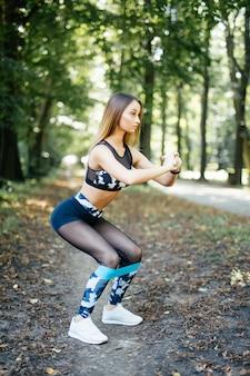 Vrouw oefenen met elastische weerstand band in het park