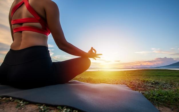 Vrouw oefent yoga buiten in de buurt van de rivier in de avond