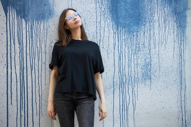 Vrouw of meisje met een zwart blanco katoenen t-shirt met ruimte voor uw logo, mock-up of ontwerp in een casual stedelijke stijl