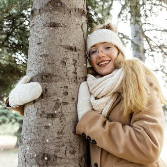 Vrouw omarmen boom in het park in de winter