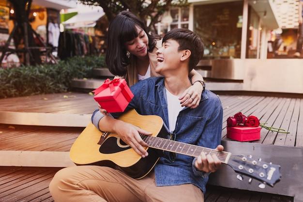 Vrouw omarmen een man en het bedrijf een geschenk terwijl hij gitaar speelt