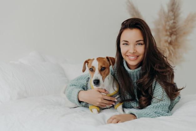 Vrouw omarmt hond met liefde, brengt samen vrije tijd door, drukt teder gevoel en emoties uit