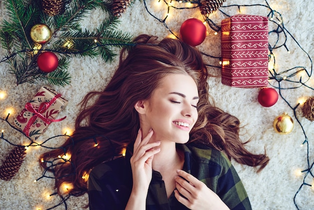 Vrouw omgeven door kerstverlichting op de vloer liggen en dromen