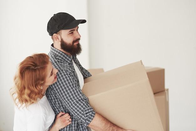 Vrouw omhelst haar echtgenoot. gelukkig paar samen in hun nieuwe huis. conceptie van verhuizen