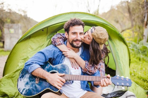 Vrouw omhelzen en kussende man met gitaar