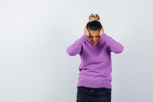 Vrouw omklemt hoofd met handen in wollen blouse en ziet er depressief uit