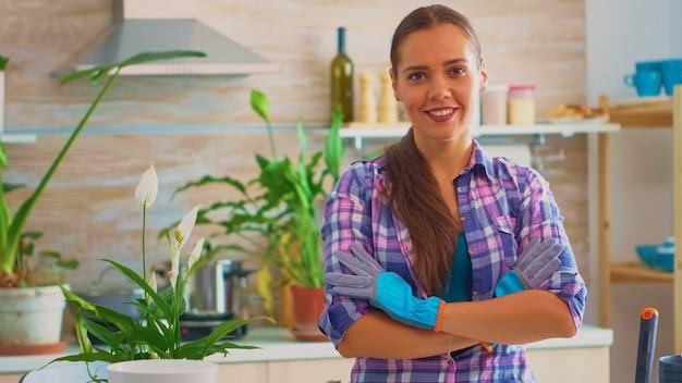 Vrouw omringd door bloemen glimlachend en kijkend naar de camera. met behulp van vruchtbare grond met een schop, witte keramische pot en kamerbloem, planten, voorbereid voor herbeplanting voor huisdecoratie.
