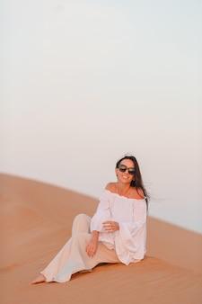 Vrouw onder de duinen in de woestijn in de verenigde arabische emiraten