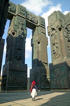 Vrouw onder de indruk van de chronicle of georgia, een enorm monument dat de oude geschiedenis van georgia country uitbeeldt