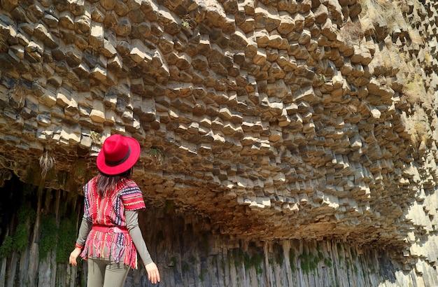 Vrouw onder de indruk van stenen basaltkolomformaties langs de garni-kloof in armenië